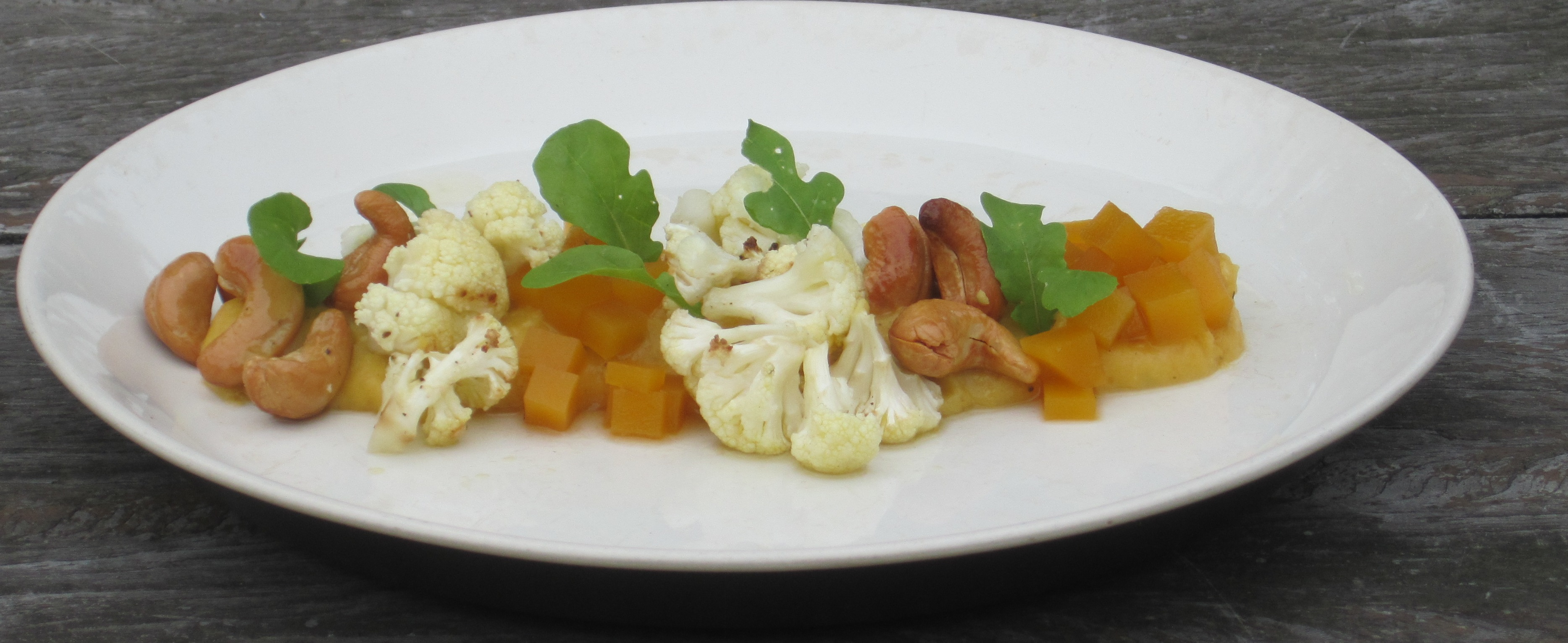 Pompoencrème met geroosterde bloemkool, zoute cashew, zoetzuur van pompoen en rucola